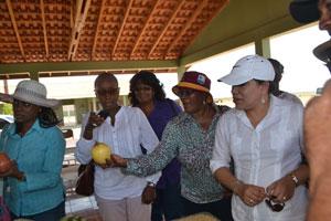 Senator Maxine McClean expresses astonishment at the size of the passion fruit produced at the Santa Fe farm