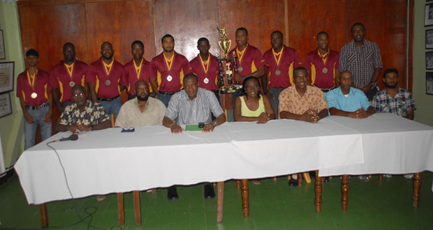 The victorious Demerara Cricket Club first division team, who are out decked in their limited overs tops, strike a pose with the GCA/Hadi's Mall Inc. first division trophy while displaying their medallions, even as the members of the head table sit in forefront. Third from left is GCA's president Roger Harper, who has Percy Hedwig on his right. (Photo by Sonell Nelson)