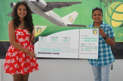 Fly Jamaica representative, Ms. Susan Razack, presenting a Boarding Pass to Go-Kart driver,  Ms. Emma Vieira, winner of a round trip ticket to Jamaica, at the recently concluded Caribbean Motor Racing Championship