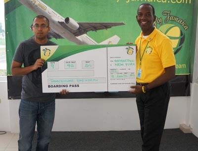 Fly Jamaica representative, Wesley Tucker, presenting a Boarding Pass to the winner of a roundtrip ticket to New York, Mr. Tameshwar Ramcharan