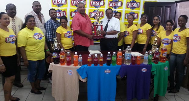 Flanked by the Busta Girls and members of staff of both the Guyana Beverage Company Inc. and Rose Hall Town Youth and Sports Club, a smiling Robert Selman (7th from right) presents the cheque to Hilbert Foster.