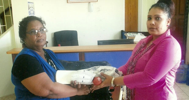 Administrative Assistant of Berbice Bridge Company Bibi Alli (right) hands over  one of the coaching kits to Secretary of the Berbice Cricket Board, Angela Haniff.