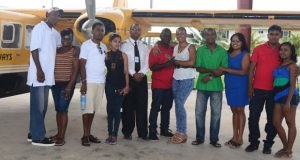 The five couples pose with the pilot before departure from the Ogle International Airport