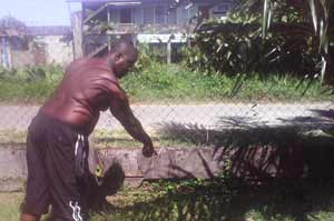 A resident points to an area in his garden which is water-logged as a result of repairs made to water lines by GWI representatives.