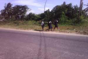 School children hurry home after school, desperate in their bid to avoid the scorching midday sun