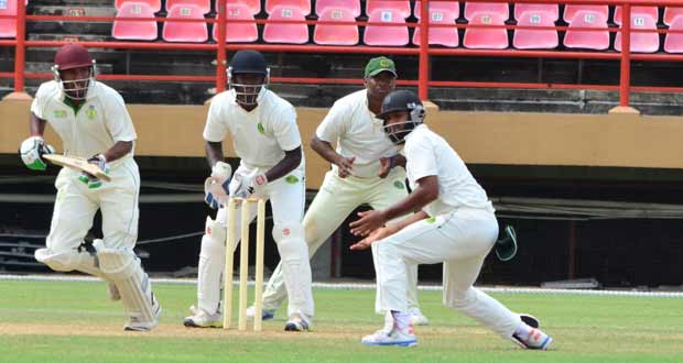 Guyana's Anthony Bramble (wicketkeeper) and Christopher Barnwell (slip) looks on as Windward Islands top scorer Romel Currency plays one past Assad Fudadin at forward short leg during yesterday's action. (Photo by Adrian Narine)
