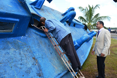 Minister of Home Affair, Clement Rohee getting a closer look at the inside of the Self-Propelled Semi- Submersible vessel which has been moved to the GDF Coast Guard Base in Ruimveldt