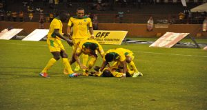Guyana's Pernell Schultz (on the ground) is swarmed by Walter Moore (right), (L-R) Joshua Brown, Neil Danns and Matthew Briggs after scoring his second goal of the game. (Delano Williams photos)