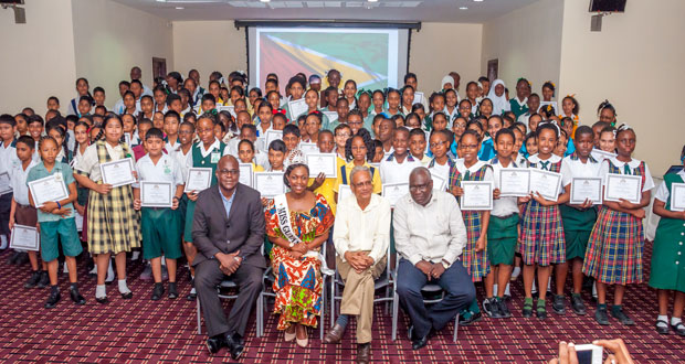 'CONGRATULATIONS!' In photo, from left, are Chief Education Officer Mr Olato Sam along with Miss Guyana United Kingdom, Zena Bland; Minister of Education Dr Rupert Roopnaraine; and chairperson of the ceremony ACEO [Primary) Mr Marcel Hutson, posing with the Top 1% students who excelled at the recent NGSA exams (Delano Williams photo)