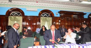 Opposition Leader Bharrat Jagdeo is applauded by his fellow MP's as he takes his seat in the National Assembly