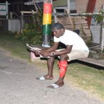 A young man reads about Baby Arthur in the Guyana Chronicle under a lamp post last evening (Delano Williams photo)