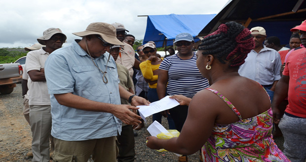 Minister of Natural Resources, Raphael Trotman, looks at a letter from miner Shavonne Justice with the names of persons who work at the site