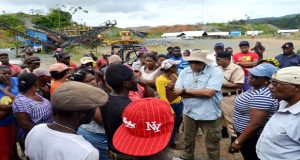 Ministers Trotman (with hat) and Broomes, at his left, interact with miners at Omai