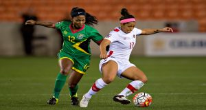 Otesha Charles (Guyana) battles Desiree Scott (Canada) for the ball at the BBVA Compass Stadium last evening.