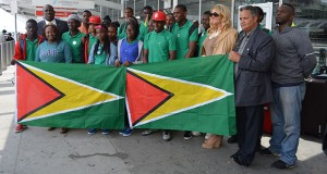 The eighteen teenagers from the Fort Wellington Secondary School stand proudly with the Guyana Flag at the John F. Kennedy International Airport, New York. Also in photograph are: Karen Kraus, Chief Operations Officer Dynamic Airways, Captain Gerry Gouveia, and Rickford Burke Chairman of Guyana's 50th Independence Anniversary celebrations.