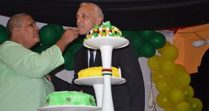 Member of Parliament Ms Rajcoomarie Bancroft sticks the region's anniversary cake with Minister Bulkan