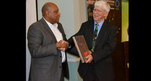 Minister of Natural Resources, Raphael Trotman, presenting a token of appreciation to Conservation International President Dr Russell Mittermeier on Monday evening