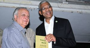 Sir Shridath Ramphal and President David Granger pose with a copy of 'Guyana in the World'