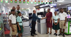 STARR Computer CEO, Mike Mohan officially hands over the equipment, seen in the background, to Deputy Headteacher, Allison Cosbert in the presence of alumni representatives Alex Neptune, Linden Branche and students