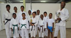 Sensei Winston Dunbar and Sadella Britton hold trophies with the other participants.