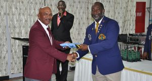 President of the Antigua and Barbuda Shooting Club, Thomas Greenaway (right) hands over the WIFBSC Flag to GuyanaNRA Captain Mahendra Persaud .