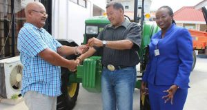 Minister of Indigenous Peoples' Affairs, Vice-President Sydney Allicock, handing over the keys to a tractor to a village toshao