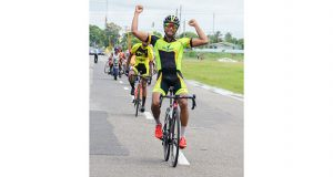 Geron Williams raises his hand in triumph even before crossing the finish line in yesterday's GCF's 71-mile road race around the outer circuit of the National Park (Delano Williams photos