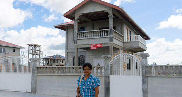 Ramdai Janet Dorie, 64, stands in front of her incomplete home