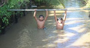 Two youngsters having a swim in one of the trenches at Sans Souci Village