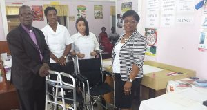 Bishop Timothy Norton of God's Cathedral of Praise (at left) presents the two wheelchairs and a walker to Medex Karen Sears (right). Looking on are nurses Dawn Miller and Anne Marie Hudson