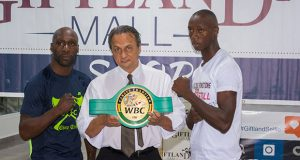 DeMarcus `Chop Chop' Corley (left) and Dexter `The Cobra' Gonsalves (right, strike a pose with GBBC president Peter Abdool who shows off the WBC's FECABOX lightweight belt that will be up for grabs tomorrow night. (Photo by Samuel Maughn)