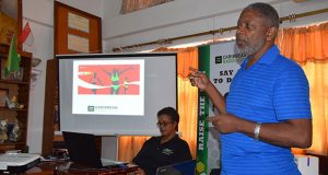 Doping Control Officer, Charles Corbin, during one of the presentations on Anti-Doping at yesterday's workshop. Sitting is Guyana's Caribbean RADO Board Member, Dr Karen Pilgrim.