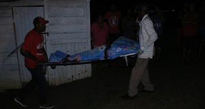 The body of 47-year old Anita 'Sandra' Mohan being removed from her lot 315 South East Cummings Lodge home on Sunday evening