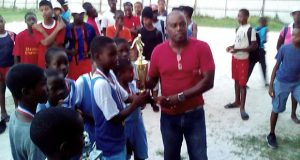 John Adams, Member of Parliament  Region Three presents winning trophy to captain of Den Amstel Primary, Stellon Nelson.