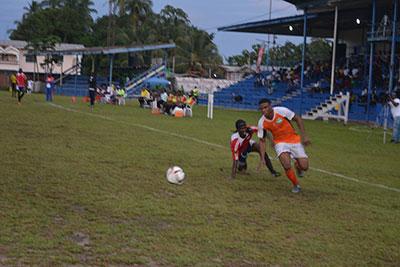 Eon Alleyne,scorer of Conquerors first goal last night,leaves Buxton's Okemi Edwards on his way to goal. (Ras Wadada photos)