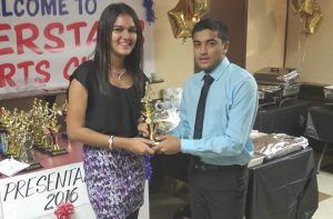 MVP Trushil Patel receives one of his several awards from female player Megan Yougnauth.