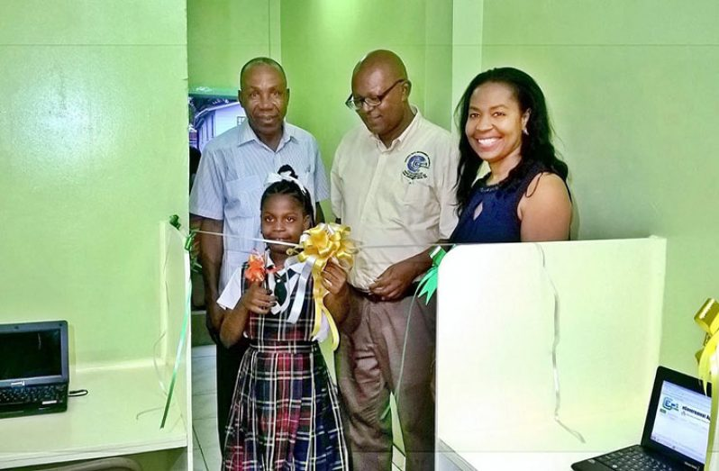 Schoolgirl, Euphoria Caesar cuts the ceremonial ribbon to officially declare the facility open. Cheering her on from left are:  Pastor Elsworth Williams of the Heavenly Light Church; NDMA Director, Mr Phillip Walcott and Councillor Carolyn Caesar-Murray