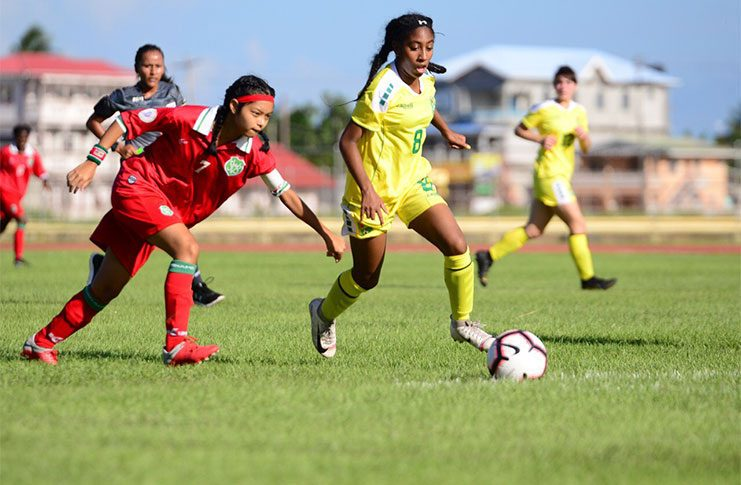 FLASHBACK! Lady Jags' Serena McDonald (#8) dribbles by Suriname's captain Cady Chin-See-Chong during Guyana's 3-1 win at the National Track and Field Centre in 2019. (Samuel Maughn photo)