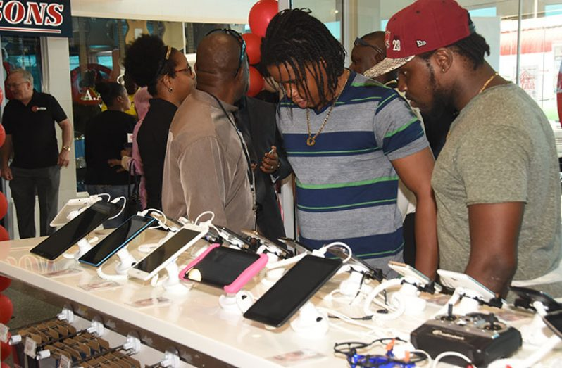 Some of the first customers of Radio Shack Guyana store examine a range of IPADs at the store at Giftland Mall, Turkeyen Friday (Adrian Narine photograph)