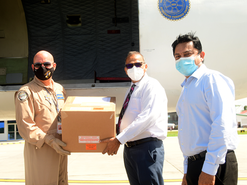Minister of Health, Dr Frank Anthony (second right) and Chief Medical Officer, Dr Narine Singh, collect the vaccines, donated by Barbados to Guyana, at the Ogle Airport, on the East Coast of Demerara (Adrian Narine photo)