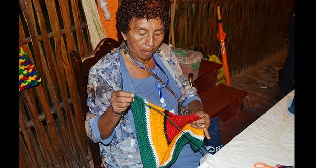 Bridget Alleyne knits an item which is made in the colours of the Golden Arrowhead