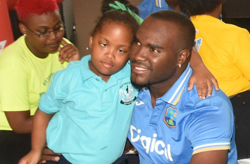 West Indies spinner Ashley Nurse shares a light moment with a student of the Gifted Hands Special Needs Children.