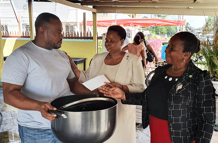 Chairman of the People's National Congress Reform (PNCR), Volda Lawrence makes a donation to the Guinness Bar and Restaurant owner, Troy Mendonca