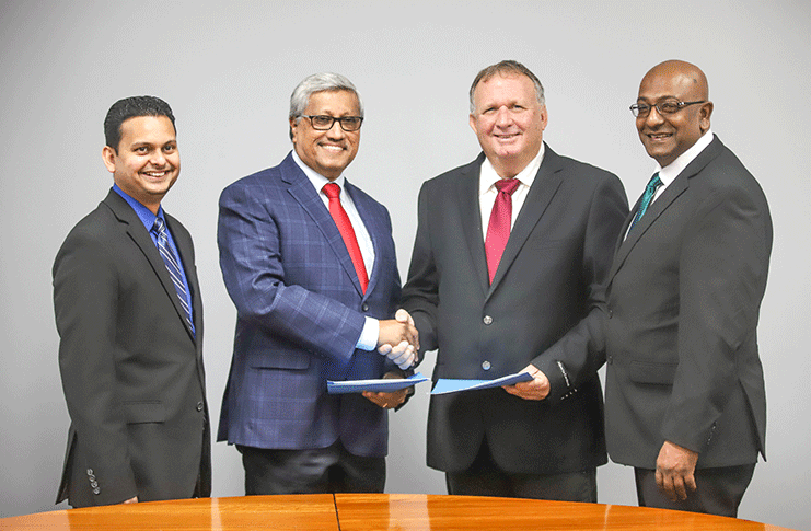 DDL Chairman, Komal Samaroo and CWSL CEO, Nigel Bennett shake hands after the signing of an agreement. Vasudeo Singh, DDL Finance Controller and Darren Debideen, CWSL Chief Marketing Officer look on