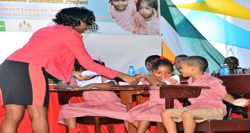 A teacher interacts with students at the launch of the Early Childhood Development Project