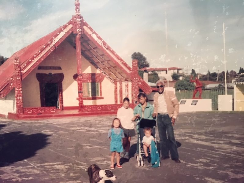 Farrier with four Maori children in front of a Maori church in New Zealand