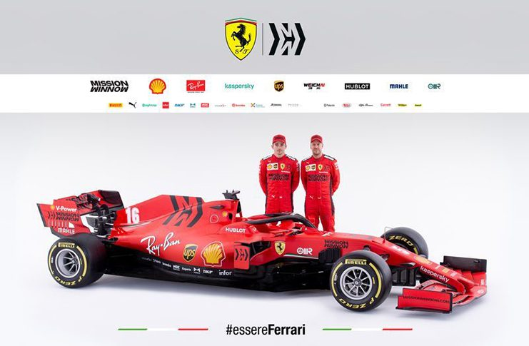 Ferrari's drivers Charles Leclerc and Sebastian Vettel pose next to the new Ferrari Formula One in this handout photo released  Tuesday. Ferrari Press Office/Handout via REUTERS