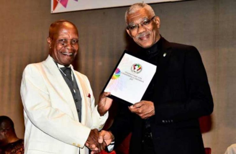 President David Granger presenting the Guyana Visual Art Competition's Lifetime Achievement Award to Jorge Bowen-Forbes at the National Cultural Centre, recently (Samuel Maughn Photo)