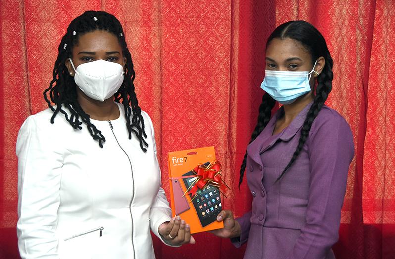 Winner Martina Johnson (left) receiving her Amazon Fire 7 Tablet from Guyana National Newspapers Limited (GNNL) marketing clerk, Tamara Tucker