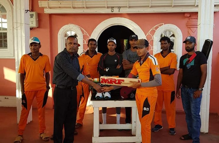 Here, Persaud (left) hands over part of the donation to Mohabir while other members of the club look on.